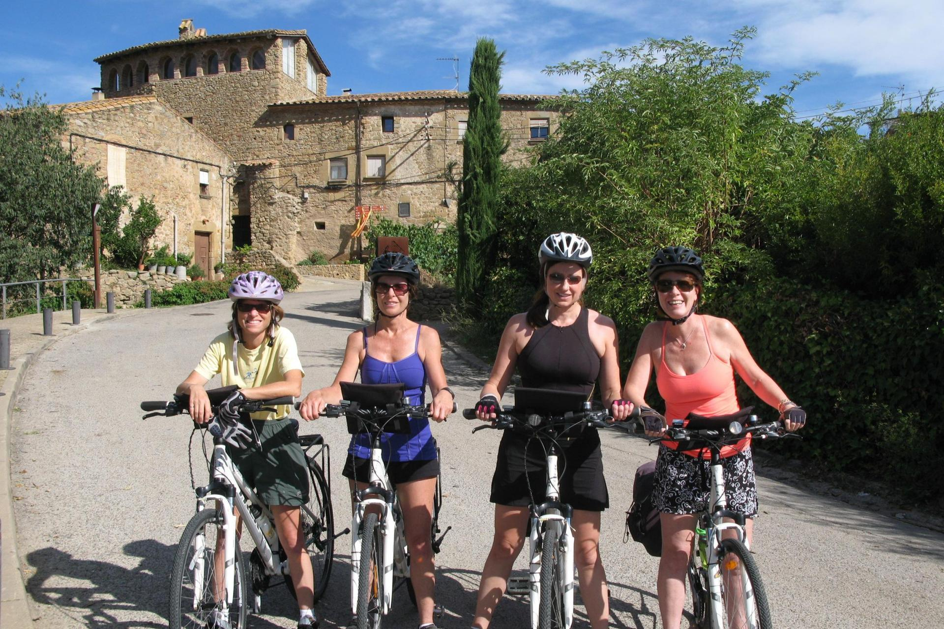 A group of cyclists on a tour stand in the foreground with medieval Spanish architecture in the background