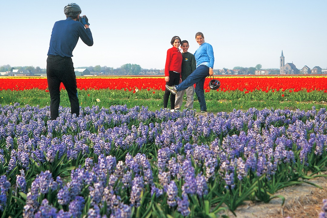 Man takes a picture of teenage girls in a tulip field