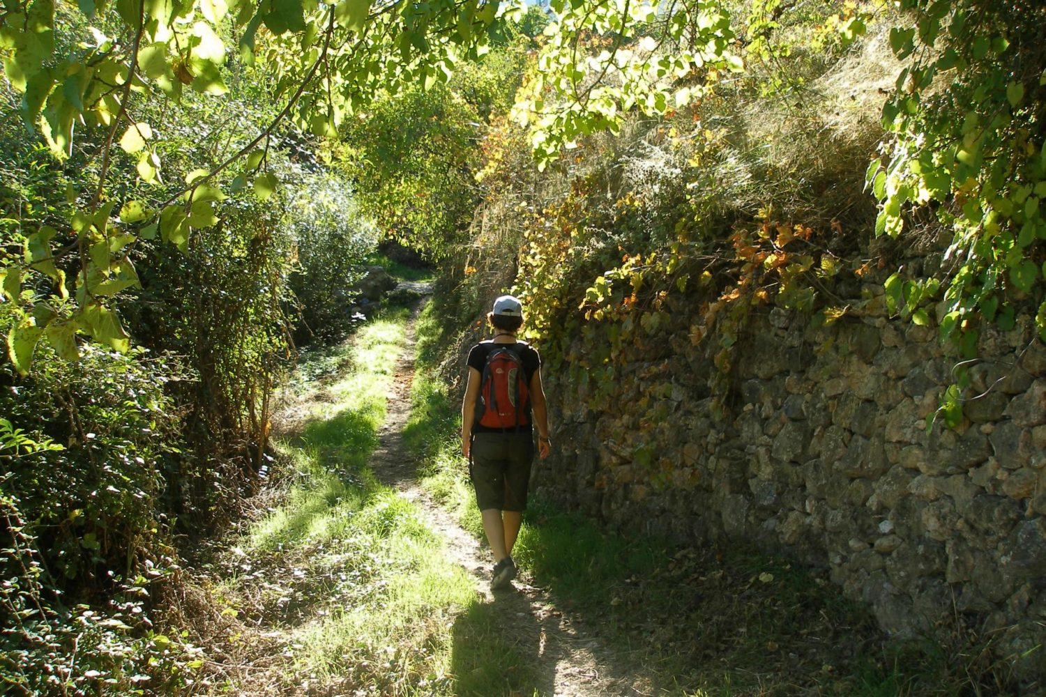 Hiker beside an old stone wall in Andalusia
