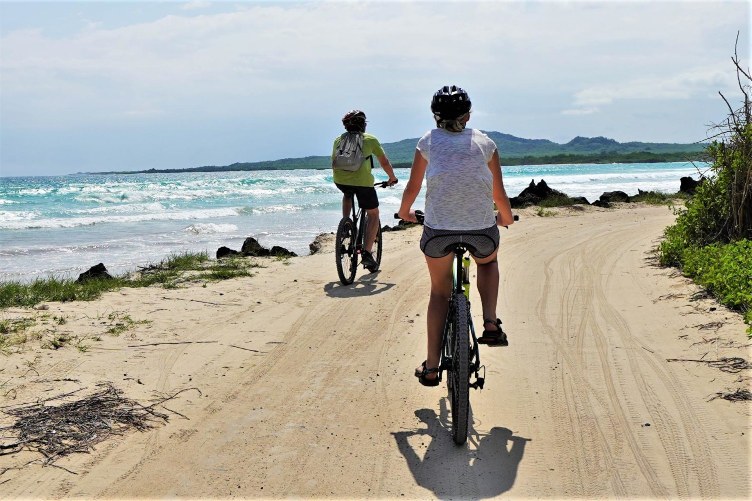 Two cyclists beside a Galapagos beach