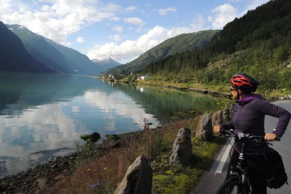 Cyclist overlooks calm waters in Norway