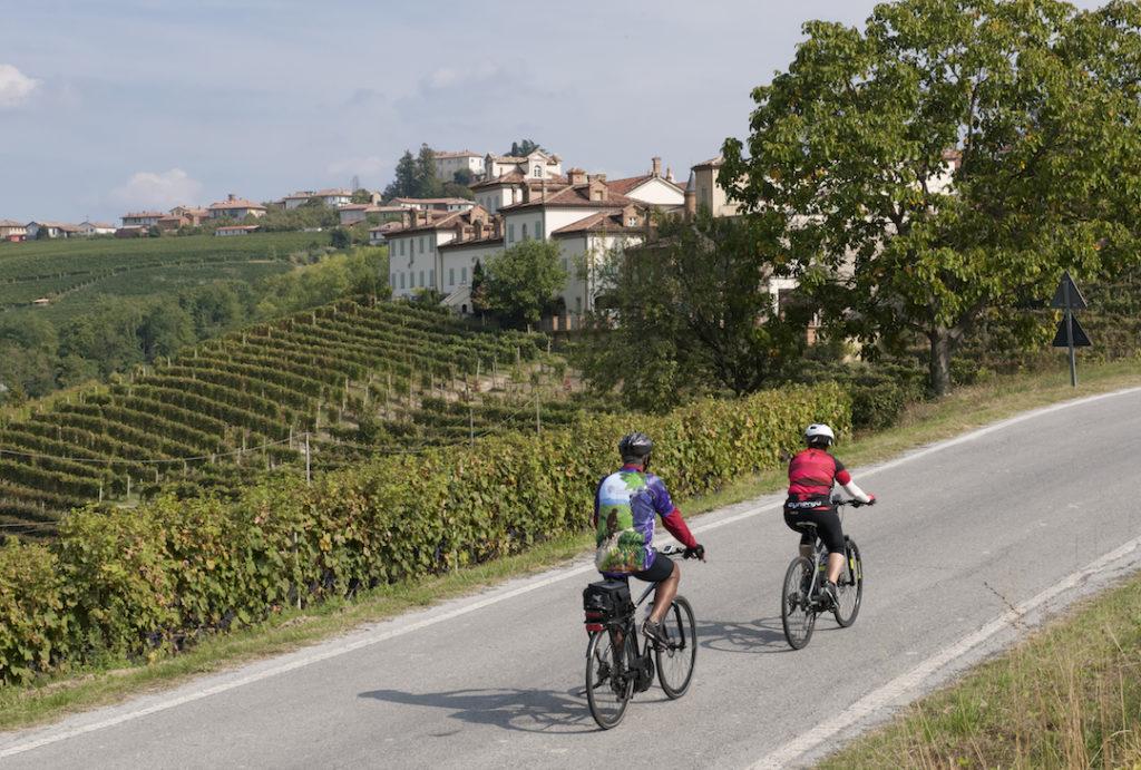 Two cyclists on e-bikes ride through the European countryside