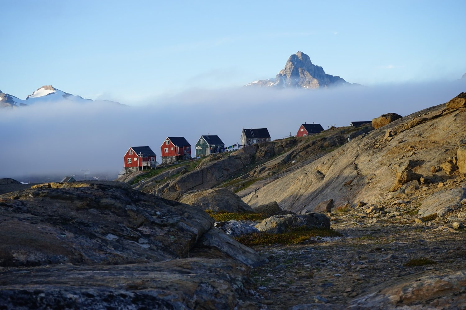 The colorful houses in Tasiilaq, Greenland amidst the rugged landscape.